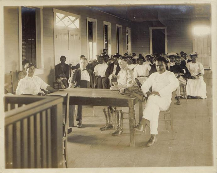 Large group of men and women seated indoors